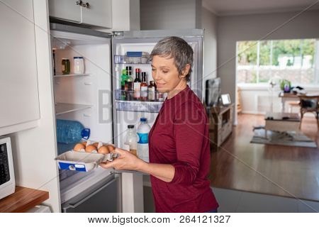 Senior woman removing eggs tray from refrigerator to prepere a pie. Mature woman holding eggs tray with open fridge to take the ingredients of the culinary recipe. Housewife preparing lunch or dinner.