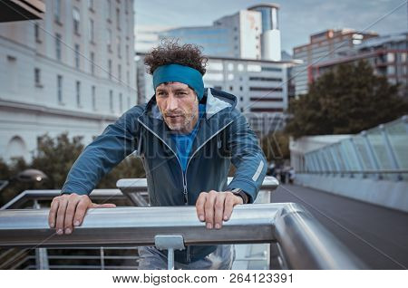 Mature jogger with headband resting after workout in a winter day. Tired runner taking breath after running in the city. Senior sport man leaning over bridge railing during early morning workout.