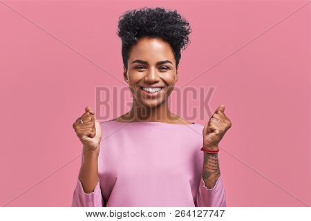 Portrait Of Overjoyed Female Clenches Fists With With Happiness, Opens Mouth Widely As Shouts Loudly