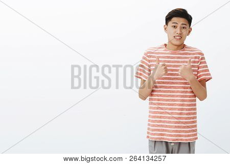 Fine I Guess. Portrait Of Unsure Awkward Young Attractive Asian Man In Striped T-shirt Making Tight