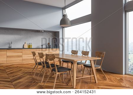 Interior Of Dining Room With Gray Walls, Wooden Floor, Long Table With Chairs And Countertops In The