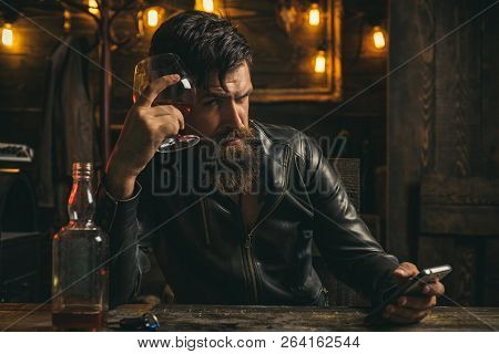 Serious sad man having alcohol addiction. Psychologist theraphy social problems concept alcohol addiction. People hands addicted by mobile smart phone. Sad bearded man with social problems poster