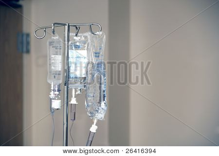 Three IV's hand on a stand in a hospital room