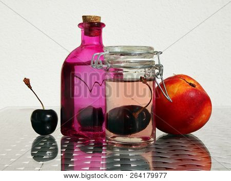 Still Life With Fresh Compote In Vintage Glass Botlles, Nectarine And Ripe Cherries Against A High K