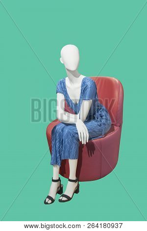 Female Mannequin Sitting On A Round Red Leather Chair Over Green Background. No Brand Names Or Copyr