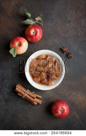 Homemade Apple Chutney (apple jam, marmalade, chunky sauce) with cinnamon, anise and apples on rustic background, close up. Traditional autumn apple jam. poster