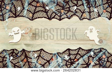 Halloween background. Black cobweb lace border and Halloween decorations in form of ghosts on the wooden background with free space for Halloween holiday text