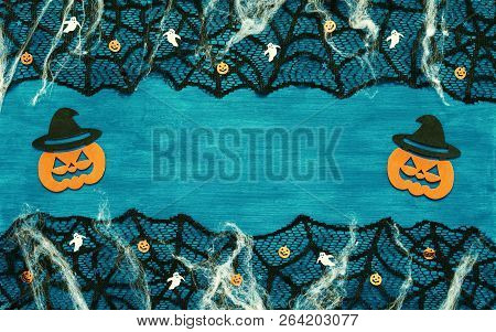 Halloween background - spider web lace, smiling jack decorations as symbols of Halloween on the dark green wooden background. Halloween festive concept