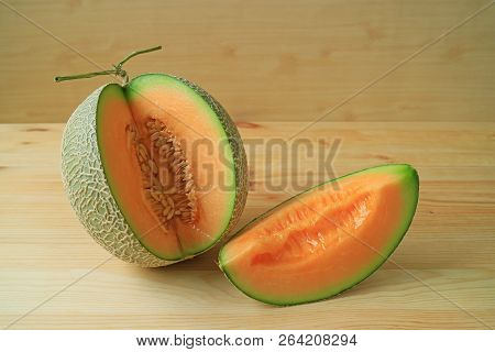 Mouthwatering Orange Color Juicy Ripe Fresh Muskmelon Sliced From Whole Fruit Isolated On A Wooden B