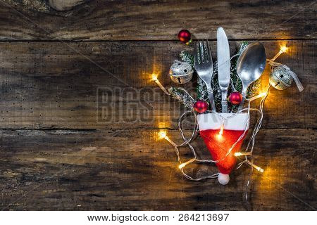 Christmas Menu Dinner Cutlery Set With Santa Claus Cap, Light And Decoration On Wooden Table Backgro