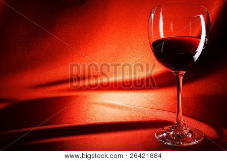 red wine glass on fabri?  background