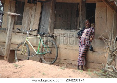 Abetifi, Ghana: July 20th 2016 - Girl Leaning On Wooden Shack Next To Bicycle In Ghana