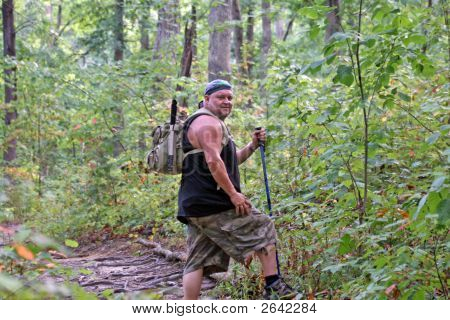 Man Wearing A Backpack & Hiking On A Nature Trail