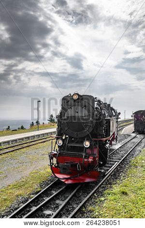 Black Locomotive With Red Color Driving On A Railtrack Under A Cloudy Sky