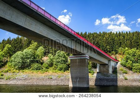Bridge With Red Fence Over A Lake In The Summer With A Forest In The Background