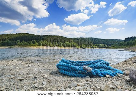 Blue Rope On A Pebble Beach In The Summer With A Large Green Forest In The Background
