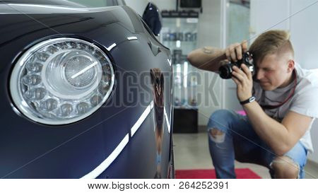 A Young Professional Photographer (a Guy, A Man) Takes Pictures Of A Car In A Car Salon. Concept: Li