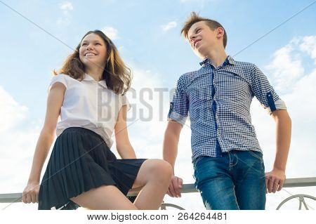 Happy Couple Of Teens Boy And Girl 14, 15 Years Old. Young People Smiling And Talking, Blue Sky Back