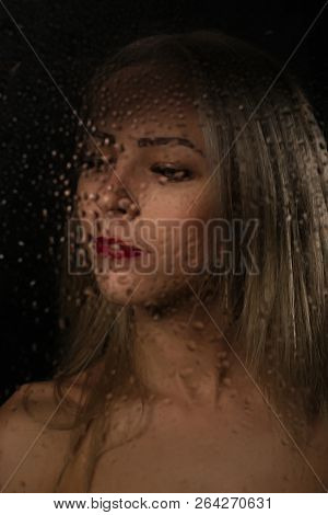 Smooth Portrait Of Sexy Model, Posing Behind Transparent Glass Covered By Water Drops.