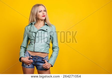 Sexy Young Woman In Leather Jacket And Short Denim Shorts Posing On A Yellow Background