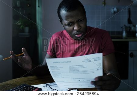 Paying Bills Concept. Stressed African American Man Do Not Understand Great Sums In His Bills, Check