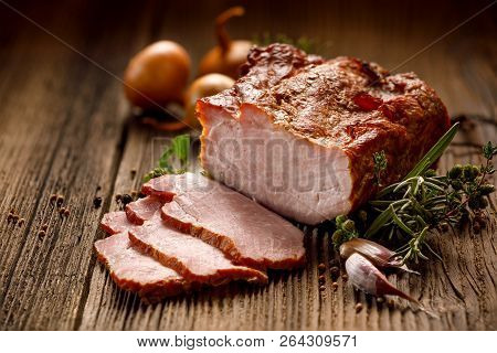 Smoked Meats, Sliced Smoked Pork Loin On A Wooden  Table With Addition Of Fresh  Herbs And Aromatic