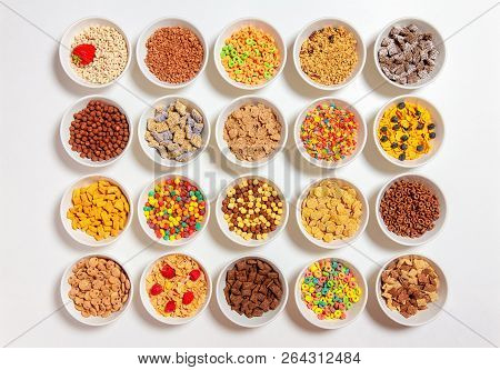 Set Of Different Cereals On A White Background. 20 Bowls With Cornflakes, Kasha, Cereals And Berries