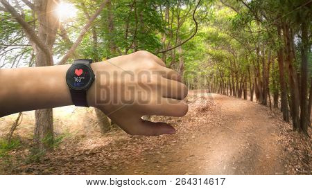 Runner Checking At Heart Rate Monitor Watch Running On Road In Forest, Color Effect