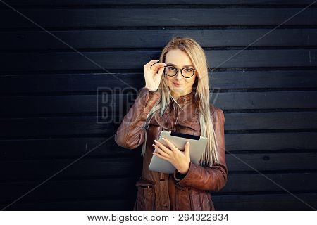 Blonde Businesswoman Using Tablet Against Black Wooden Background. Wearing Brown Leather Jacket And