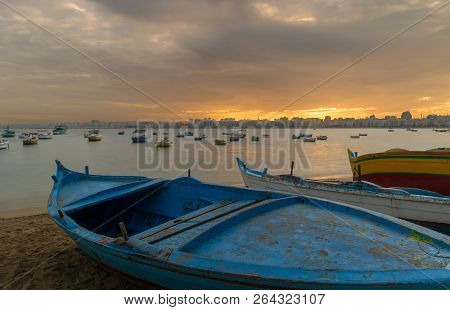 Turquoise Blue Fishing Boat On The Beach At Sunrise With Alexandria Skyline In Far Distance And Colo