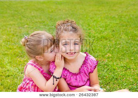 children girl sister friends whispering ear in green grass park