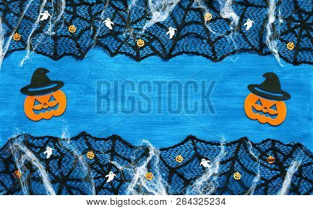 Halloween background - spider web, spiders, ghosts and smiling jack decorations as symbols of Halloween on the dark blue wooden background. Halloween concept, free space for text