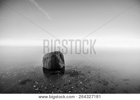 Single Rock In The Water By The Sea In Black And White Colors