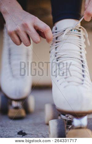 Image Of Woman Tying Laces On Rollerskate
