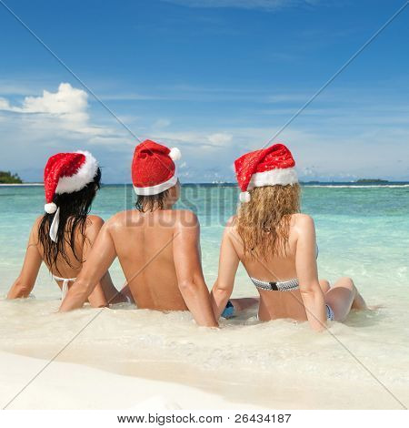 Happy friends in santa hats on the beach. Christmas vacation