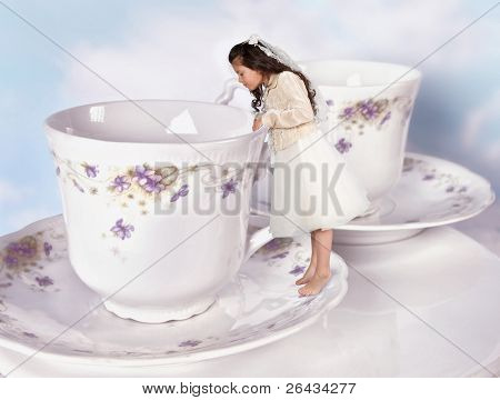 Miniature girl in alice in wonderland dress shrunk to the size of a teacup