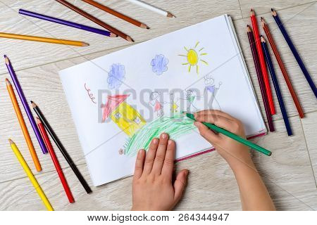 The Child Draws His Family On A Piece Of Paper With Colored Pencils. What Can A Childrens Picture Te