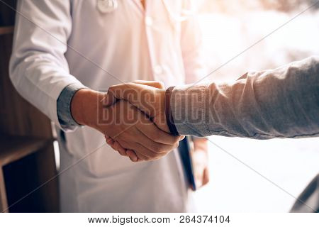 Doctor Shaking Hands With Patient In The Clinic.