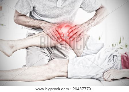 Highlighted pain against male physical therapist massaging patient knee