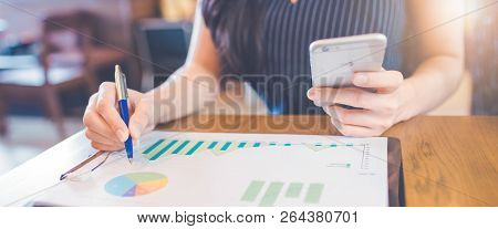 Woman Hand Writing On Charts And Graphs That Show Results With A Pen And Using A Smartphone.web Bann