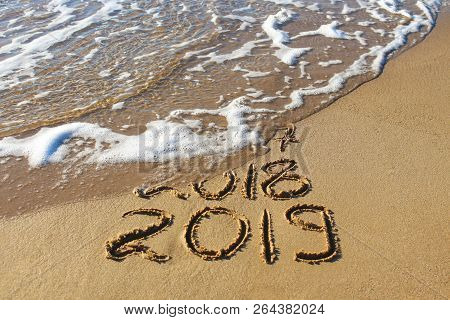 2019, 2018 And 2017 Years Written On Sandy Beach Sea. Wave Washes Away 2017, 2018.