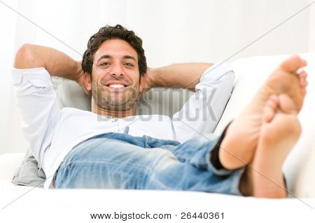 Smiling healthy young man relaxing on sofa and looking at camera