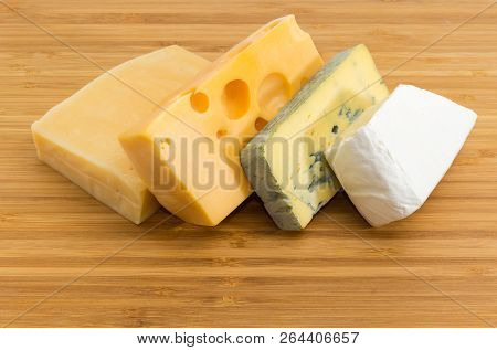 Pieces Of Blue Cheese, Brie, Medium-hard Swiss And Hard Cheese On The Bamboo Cutting Board Close-up