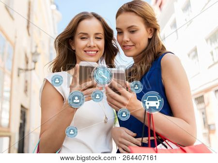car sharing, modern technology and people concept - happy young women with shopping bags and smartphones on city street