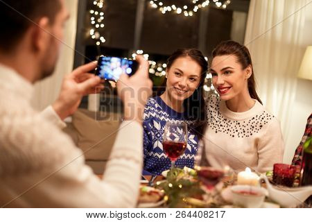 holidays and celebration concept - happy friends having christmas dinner at home and taking picture by smartphone