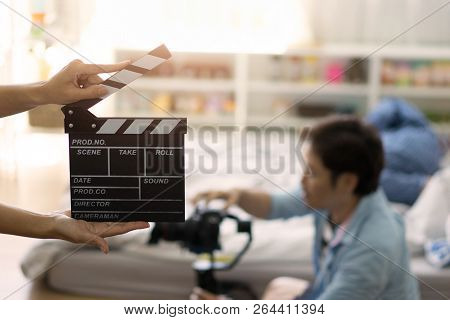 Hand Holding Clapper Board On Blurred Movie Director