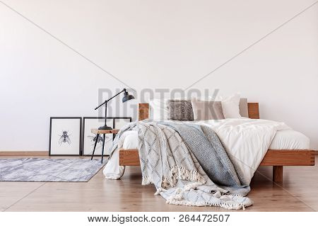 Comfortable King Size Bed With Pillows And Blankets In Bright Bedroom Interior With Rustic Carpet On