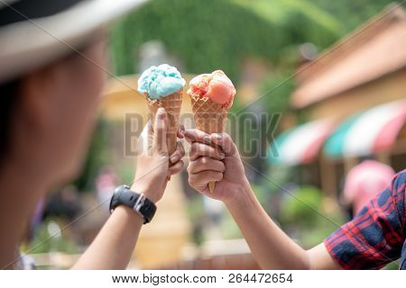 Closeup Of Hands Holding Ice Cream Cone Shown At Sunset In Summer Day On Vacation; Strawberry And Bl