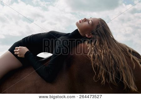 Girl Rider Lies Bent On A Horse In The Field. Fashion Portrait Of A Woman And The Mares Are Horses I