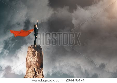 Side View Of Super Hero Woman With Cape Standing On Cliff. Dull Sky Background. Confidence And Chall